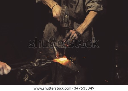 Blacksmith working metal with hammer on the anvil in the forge - stock photo