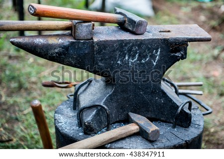 blacksmith works on an anvil. Master forges product. Tools and blacksmith anvil. Blacksmith working outdoors. - stock photo