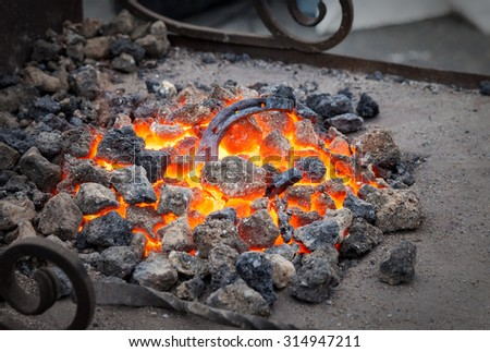 Blacksmithing, metal horseshoe is heated in the forge on coals - stock photo