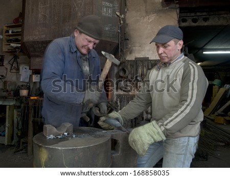 Blacksmiths at work in a small blacksmith