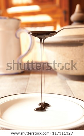 Blackstrap molasses drizzling from a teaspoon - stock photo