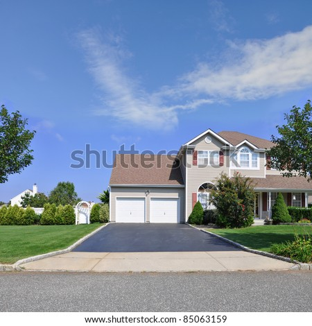Blacktop Driveway of Split Level Suburban Home with Double Garage Door Two Story Residence in Residential Neighborhood - stock photo