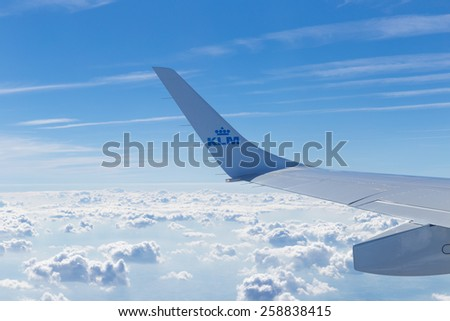 BLAGNAC, FRANCE - JULY 27, 2014: Wing section of a KLM Fokker 70 in flight. The wingspan of the Fokker 70 is 28 meter or 92 feet and 2 inch. - stock photo