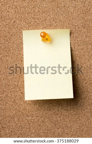 Blank adhesive label pinned on bulletin board - vertical image