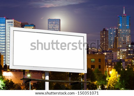Blank advertising billboard sign against downtown city skyline - stock photo