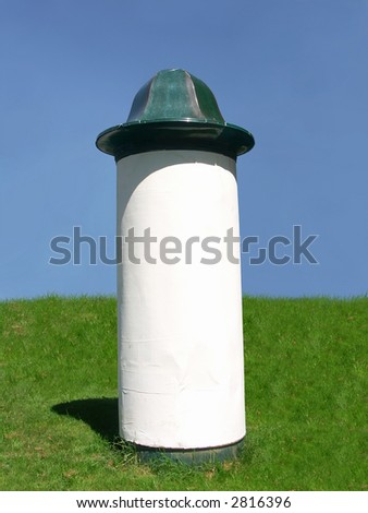 Blank advertising column waiting for advertisement to be added - against clear blue sky - stock photo