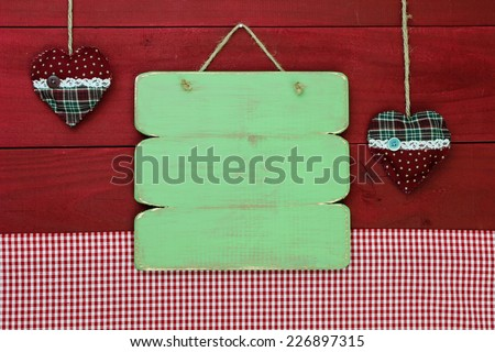 Blank antique green weathered sign by red gingham tablecloth and plaid county hearts hanging on red wooden wall - stock photo