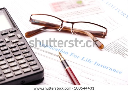 Blank application for life insurance with fountain pen, calculator and glasses. Other documents like ID etc in the bacground - stock photo