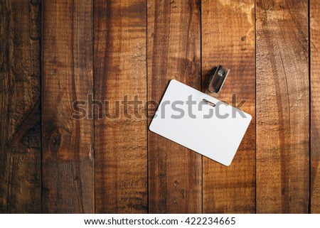 Blank badge on vintage wooden background. Blank plastic id card. Blank white plastic badge. Top view. - stock photo