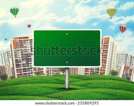 Blank billboard amidst green hills, against high-rise buildings, a few air baloons above, Curved Earth - stock photo