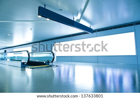 Blank billboard and modern escalator at a international airport  - stock photo