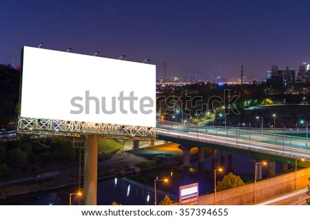 Blank billboard for advertisement in city downtown at night. - stock photo