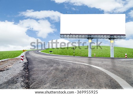 Blank billboard for your advertisement  with space for text on road curve,with green grass and blue sky white cloud  - stock photo