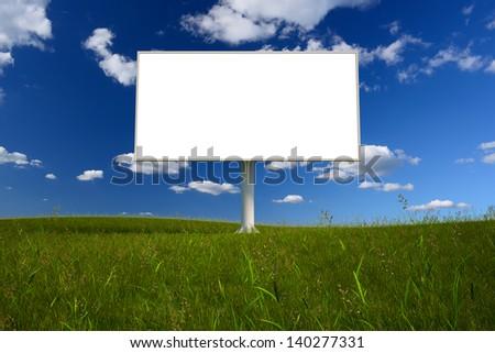 Blank billboard in a field with a blue sky - stock photo