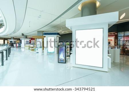 blank billboard in hallway of modern shopping mall - stock photo