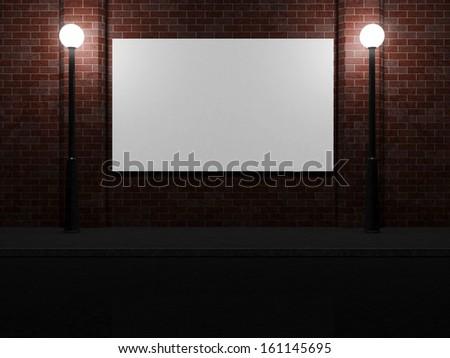Blank Billboard on a Brick Wall at Night illuminated by Street Lamps - stock photo
