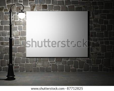 Blank billboard on a brick wall illuminated by streetlight - stock photo