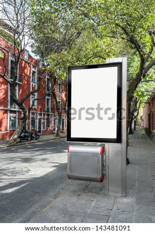 Blank billboard on a tree lined street - stock photo