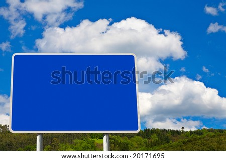 Blank billboard on blue sky in a mountainous area, just add your text - stock photo