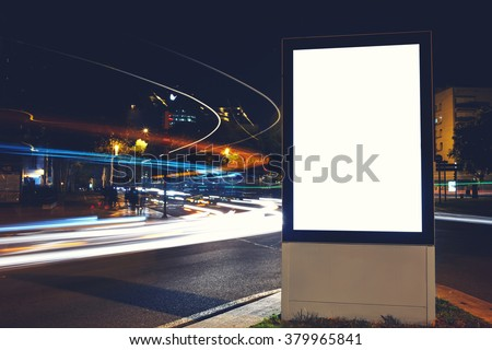 Blank billboard with copy space for your advertising text message or content, public information board in night city with shutter speed on background, empty promotional mock up Light-box on roadway - stock photo