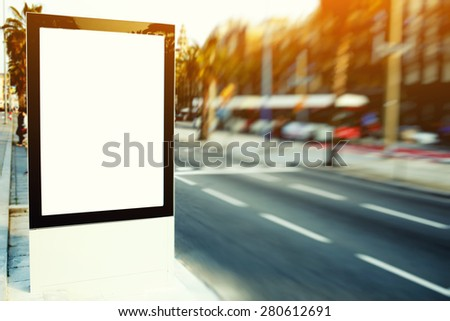 Blank billboard with copy space for your text message or content, outdoors advertising mock up, public information board on city road, flare sun light and motion blur effect - stock photo