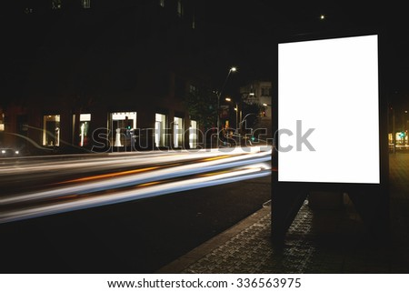 Blank billboard with copy space for your text message or promotional content, public information board in night city with shutter speed on background, empty advertising mock up banner on roadway  - stock photo