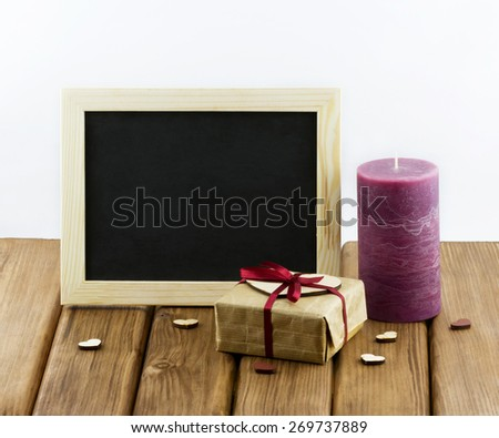 Blank blacboard with purple candle, gift box and hearts on wooden background