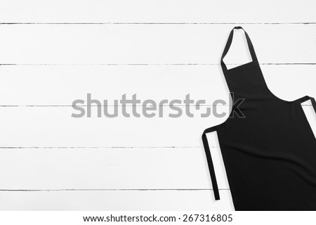 Blank black apron on white wooden background with copy space - stock photo