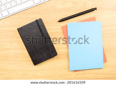 Blank Black,blue and orange notebook ,pen and keyboard on wooden table , Mock up for adding your design - stock photo