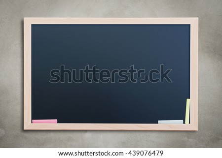 Blank black chalkboard on concrete wall with color chalk. Blank copyspace for your text or design.  - stock photo
