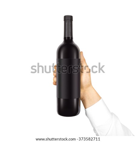 Blank black label mockup on black bottle of red wine in hand isolated. Alcohol bottle mock up presentation ready for logo design. Full drink bottle template with empty sticker. Clear tag vine bottle. - stock photo