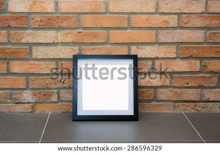 Blank black picture frame on the old brick wall and the grey floor. - stock photo