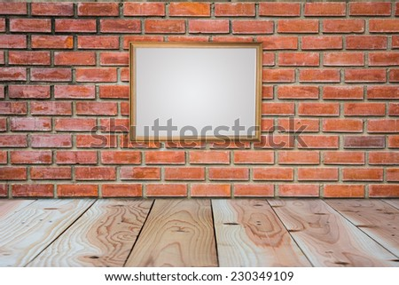 blank black picture frame on the old brick wall and the wooden floor, background  - stock photo