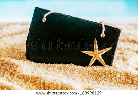 Blank black sign with copyspace for your text or advertisement nestling on golden sea sand on a tropical beach in summer with a starfish and ocean backdrop - stock photo