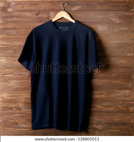 Blank black t-shirt against wooden background
