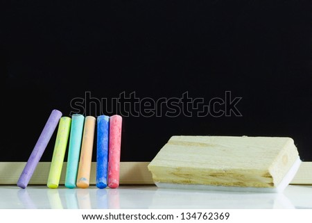 Blank blackboard and colored Chalk with blank blackboard eraser - stock photo
