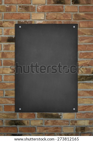 Blank blackboard at a brick wall background with space for text - stock photo