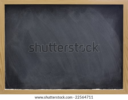 blank blackboard in wooden frame with white chalk dust and eraser smudges