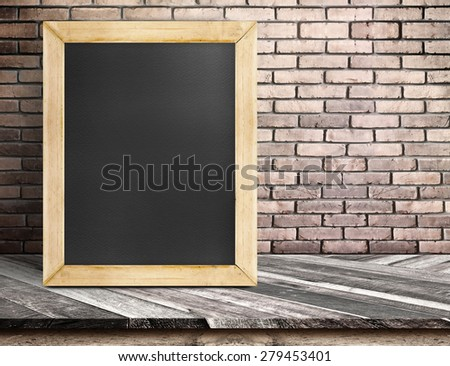 Blank blackboard on diagonal wooden table at red brick wall,Template mock up for adding your design and text. - stock photo
