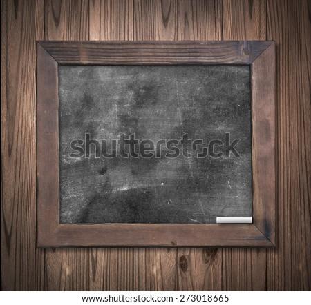 Blank blackboard on wood background. - stock photo