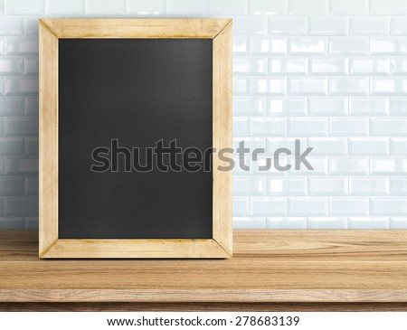 Blank blackboard on wooden table at white tile wall,Template mock up for adding your design and leave space beside frame for adding more text. - stock photo