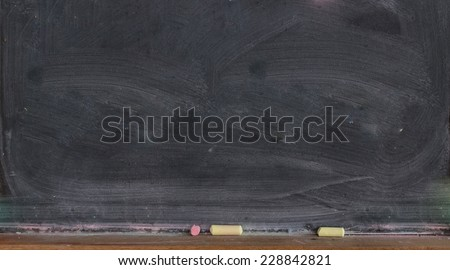 Blank blackboard with colored chalks - stock photo
