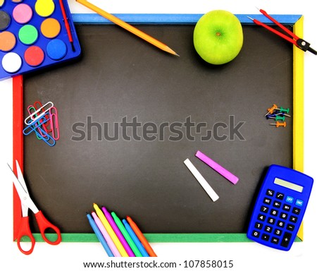 Blank blackboard with various colorful school supplies surrounding it