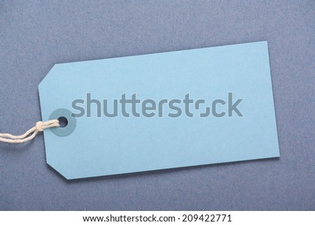 Blank blue luggage or gift tag on a complimentary blue paper background with copy space