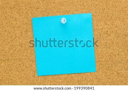 Blank blue post it paper pinned on a cork bulletin board. - stock photo
