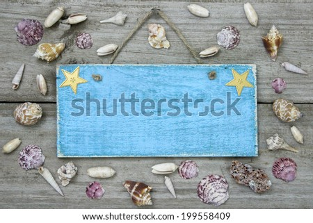 Blank blue sign with seashells hanging on rustic wooden background - stock photo