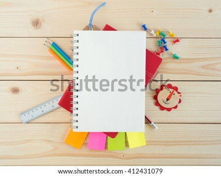Blank book and colorful stationery on the wooden table for copy space - stock photo