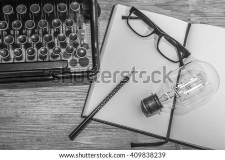 blank book, antique typewriter with reading glasses and a light bulb - stock photo