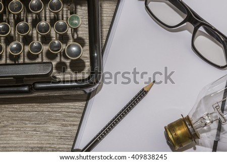blank book, antique typewriter with reading glasses and a light bulb