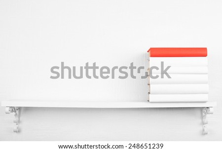Blank books with red one on bookshelf on white wall background - stock photo